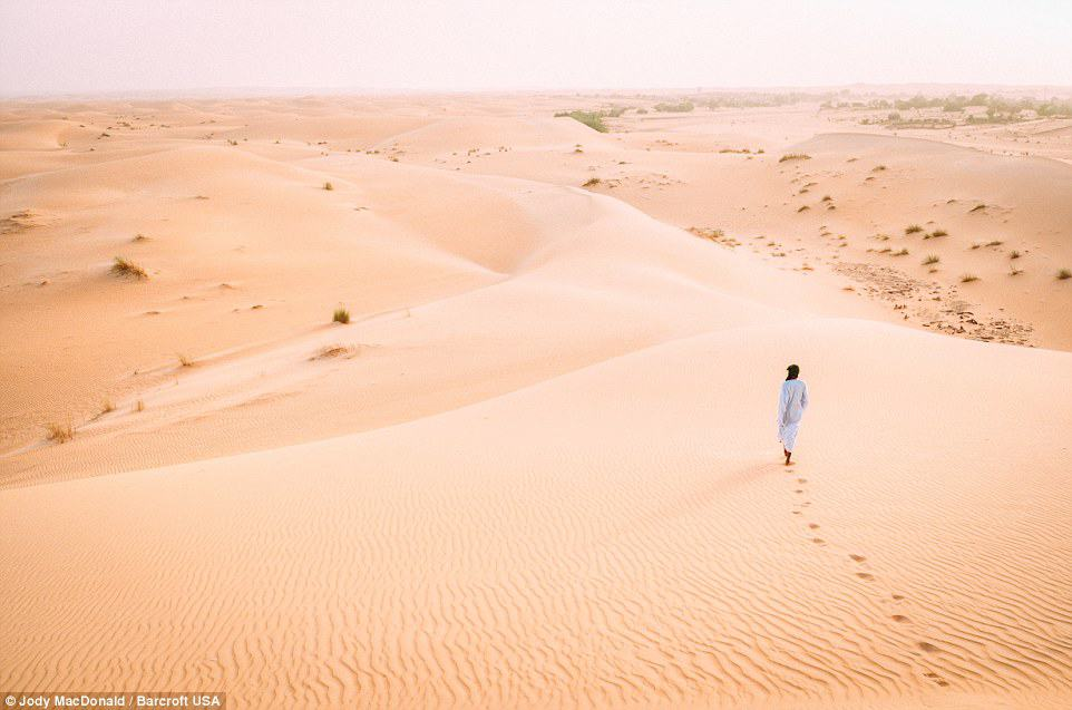 A Mauritanian man walking into the vastness of the Sahara desert