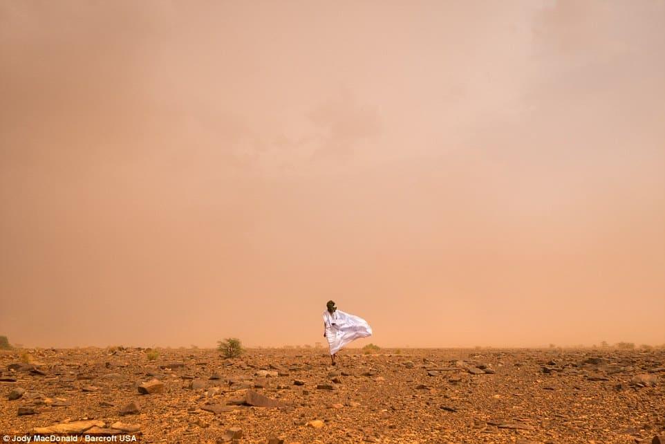 A Mauritanian man walking through a sand storm in the Sahara desert.