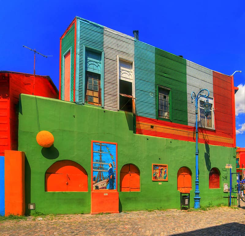 La Boca is a neighbourhood of Buenos Aires, the capital of Argentina. La Boca has many buildings made of scrap materials from the nearby shipyard that were painted lively with leftover paints from the same shipyard.