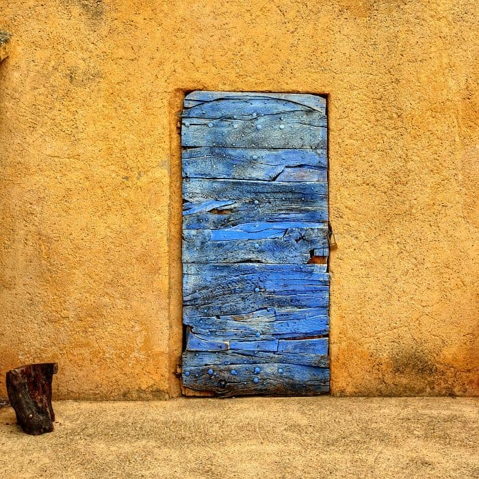 Lavender color medieval wooden door on an ocher color plastered wall. Roussillon village, Provence, France