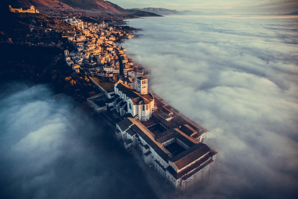 Basilica of Saint Francis of Assisi, at sunset with fog around. Assisi (PG), Umbria, Italy